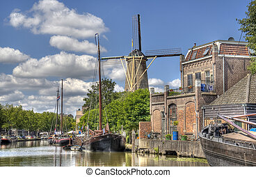 Windmill and historical boats in a canal in Gouda, Holland