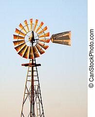 Windmill in Setting Sun - A midwestern widmill glows warm in...