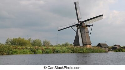 Old traditional windmill spinning in the wind by a dutch canal