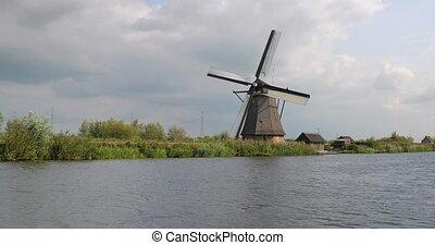 Old windmill spinning in the wind by a dutch canal