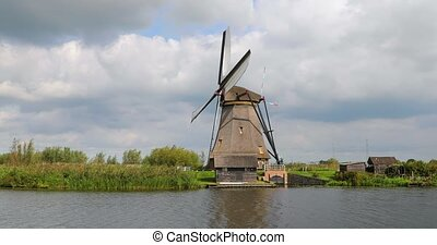 Traditional windmill spinning in the wind by a dutch canal