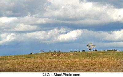 Windmill on a California hillside under a cloud filled sky