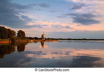 windmill on lake at sunset