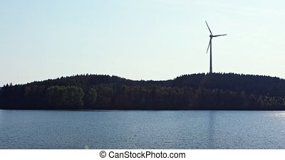 Windmill over lake - Clean renewable energy from wind and...
