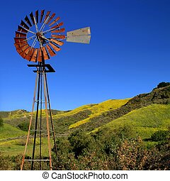 Windmill with a green and yellow spring field in the...