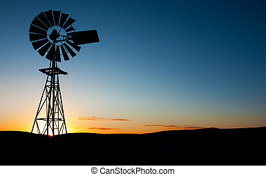Windmill Sunrise - Sun rises behind a windmill