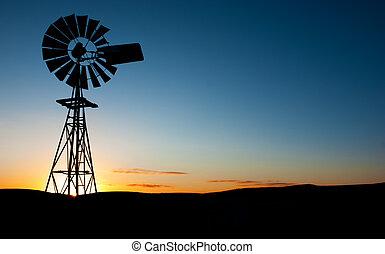 Sun rises behind a windmill