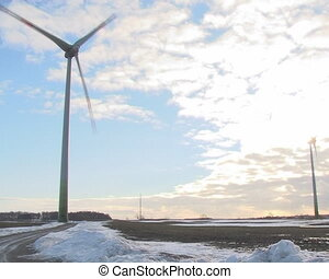 windmill and clouds in sun illuminated sky. Alternative renewable wind energy.
