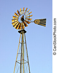 Windmill with metal blades up on a metal tower - water...