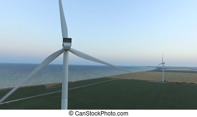 Windmills along the coast in green fields under blue skies. Aerial survey. Close up