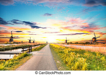 Windmills and water canal in Kinderdijk, Netherlands. Beautiful sunset sky