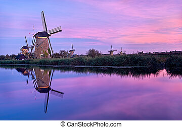 Windmills and reflection at dramatic sunset in Kinderdijk, Holland