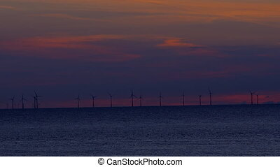 windmills at sunset in the sea