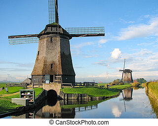 Windmills by a blue canal in the Netherlands