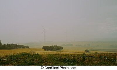 windmills covered by rain - thunderstorm with heavy rain and...