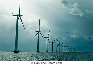 Windmills in a row on cloudy weather