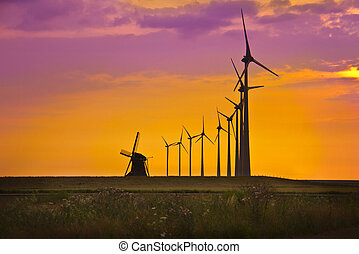 Windmills in front of bright sunset sky