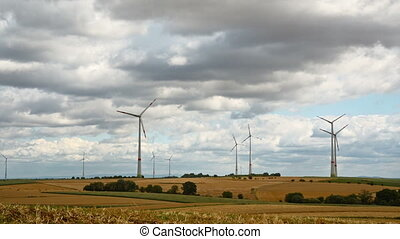 windmills in Germany in rural area - cloudy sky with strong...