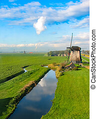 Windmills near a blue canal in the Netherlands