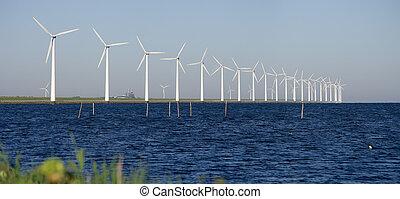 windmills on a dutch dike - row of windturbines along the...