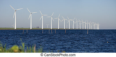 windmills on a dutch dike - row of windturbines along the...