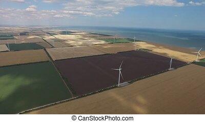 Windmills produce lot energy against a beautiful landscape. Aerial survey