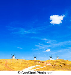 Windmills, rural green fields, blue sky and small cloud. Consuegra, Spain