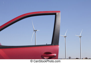 windmills through the window of a red car