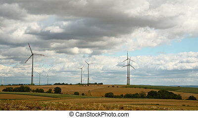 windmills with cloudy sky - cloudy sky with strong winds at...