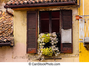 An old balcony with some yellow and white flowers