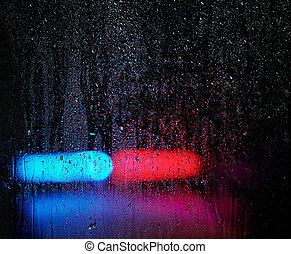Window and water drops, emergency lights on background