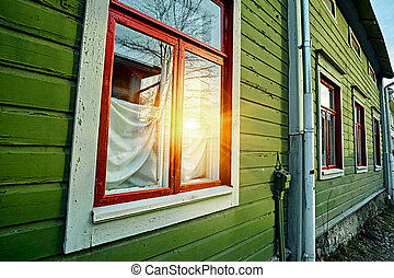 Window at the wooden green wall of traditional old vintage rural cottage house in Finland countryside village. Sun flare