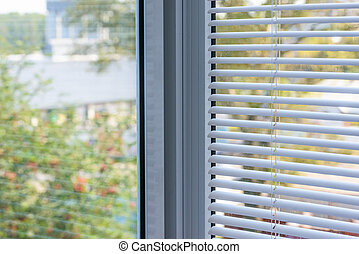 window blinds - closed plastic blinds on the window with the...