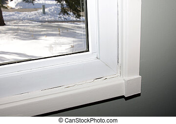 A window with damaged caulking, shot with snow visible through the window.