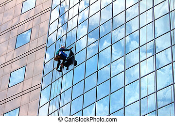 window cleaner at work - window cleaner hanging on rope at ...