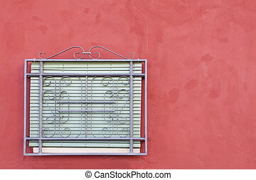 window grille and red shutters on whitewashed wall
