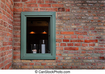 window in a brick wall with candles