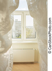 Window in a light room through the transparent tulle curtains. Picture taken at the morning in sunny day