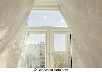 Window in a living room through the transparent tulle curtains. Picture taken in the morning in sunny day