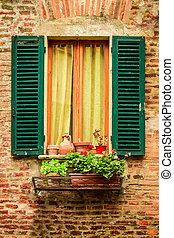 Window in an old house decorated with flower pots and...