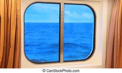window in ship cabin with dark blue ocean, cloud and sky