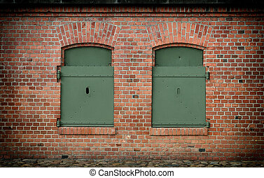 window in the brick wall and old steel shutters closed
