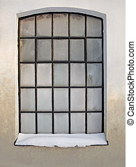 Window with twentyfive small and frosty leaded panes and with snow on the windowledge.