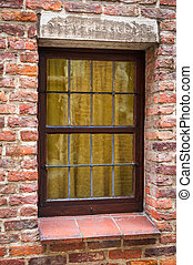 Window of a medieval building with old brick wall