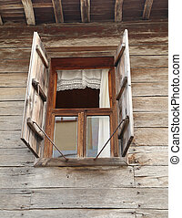 Window of a old wooden house with shutters