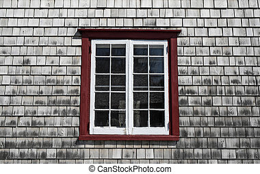 Window of an old country house with wooden tiled walls.