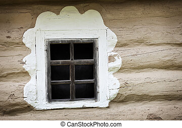 Window of ancient Ukrainian hut. Clay covered wall