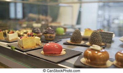 Window of cake shop with variety of cakes on display. Pastry...