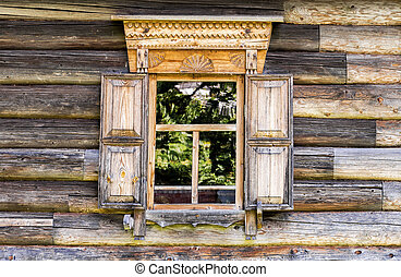 Window of old log house with carved wooden trim
