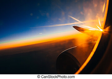 window of the airplane on the wing and turbine at sunrise against the cloudy sky in height